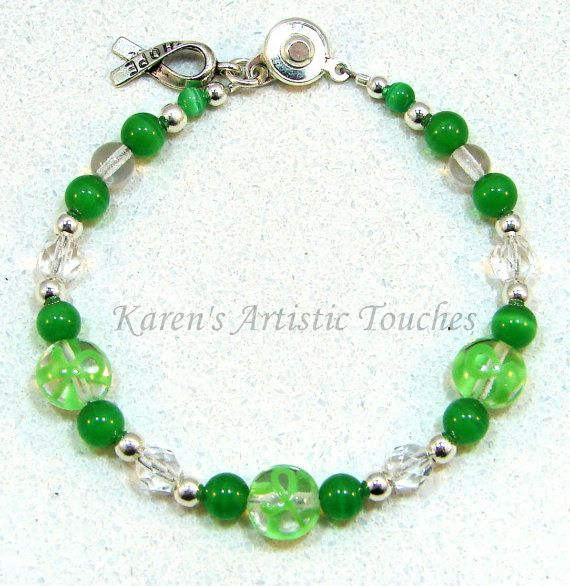 """Green Ribbon Lymphoma Cancer Awareness Bracelet Show Your Support with this beautiful bracelet! Bracelet measure 7 1/2"""". Bracelet is made using clear coin lampwork glass beads with green ribbons on the beads, green cats eye glass beads, clear faceted Czech glass beads, and silver"""