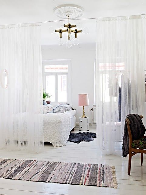 the use of sheer curtains to divide spaces in the room. good idea for studio apt.