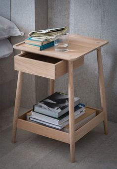 A contemporary bedside table in white oak. With a dovetailed drawer, turned legs, and a lipped bottom tray. Harlosh Bedside Table from Pinch Design.