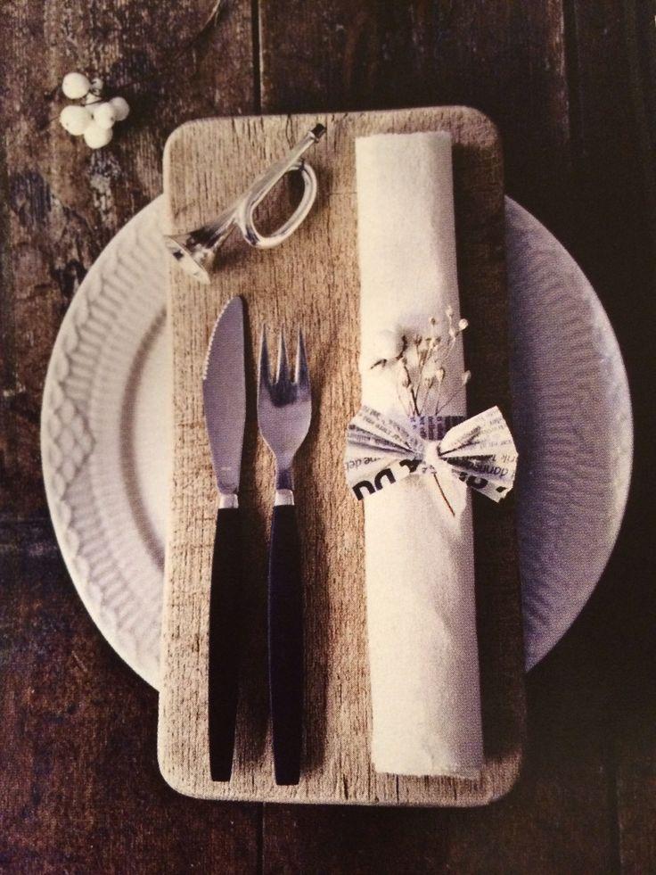 Søt serviettring av avispapir.  Du trenger: papp eller kartong, stiftemaskin, avispapir, lim, en liten stilk med visne frøkapsler og bånd. DIY: klipp et ca 3 cm bredt og 8-10 cm lagt stykke kartong/papp og avispapir i samme str. Lim avispapiret på kartongen og stift endene sammen til en serviettring. Klipp et kvadrat av avispapiret og samle det på midten med et bånd, så det ligner en sløyfe el liten vifte. Lim sløyfen på serviettringen. Putt inn en rullet serviett og pynt med den lille…