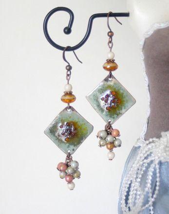 Boucles d'oreilles composées d'une plaque centrale, de 2.5cm sur 2.5 cm, en cuivre émaillée dans les teintes vert et marron avec émaux dans les tons marrons au milieu (création atelier Verre-et-cuivre). Dans le bas de la plaque, une grappe de perles satinées dans les tons vert, marron et beige clair. Dans le haut, une jolie perle en jade incrustée marron-beige clair, un petit palet dentelé en cuivre, et une perle satinée beige clair. 6.5 cm de longueur, FDP offerts.