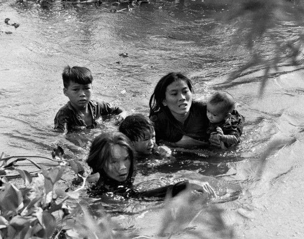 Vietnamese mother and children flee village bombing in Qui Nhon, South Vietnam. September 7, 1965