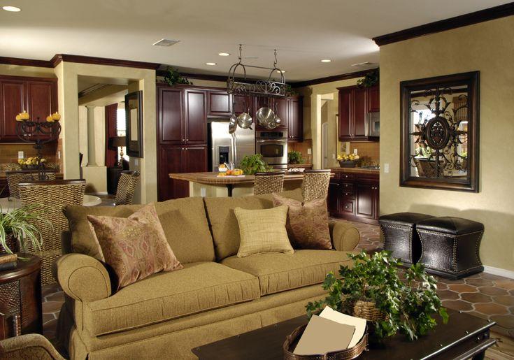 Lush gabinetes de madera de cerezo en toda la zona de la cocina en este contraste espacio abierto para compartir, con paredes de color beige y suelos de azulejos, mientras que el sofá brazo rollo marrón y tabla de pares de café de madera oscura con los otomanos de cuero individuales.