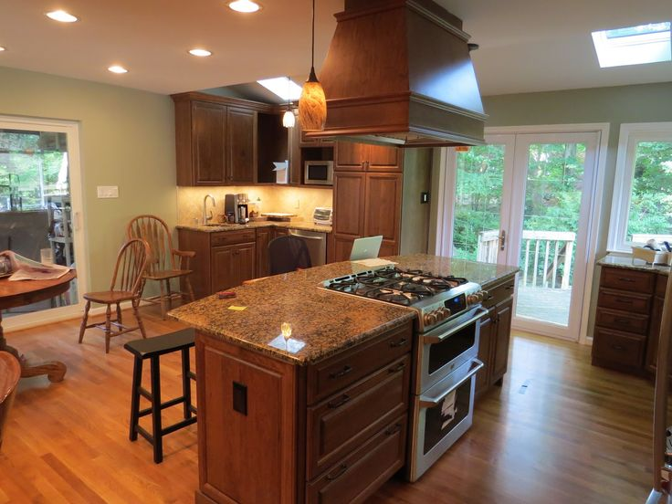 Chalkboards on the refrigerator provide a place for busy fam. Wooden Kitchen Island With Modern Stove Top On Glossy Brown Marble | Kitchen island with