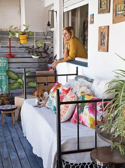 Balcón súper cálido y joven en la casa de la bloggera Lulu Biaus. Una cama antigua de una plaza hace las veces de banco y chaise longe para descansar al aire libre.