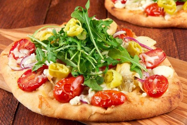 "Does ""Pizza Night"" at your house usually mean a call to the nearest greasy joint and some awkward face-time with the delivery guy? We can do you one better with these personal pizzas on delightfully chewy naan that can be whipped up in a flash. We start with grape tomatoes, juicy artichoke hearts, creamy mozzarella, and tangy goat cheese. Things get zesty with perfectly spiced pepperoncini and arugula salad on top for a simple, satisfying weeknight meal - no tip required."
