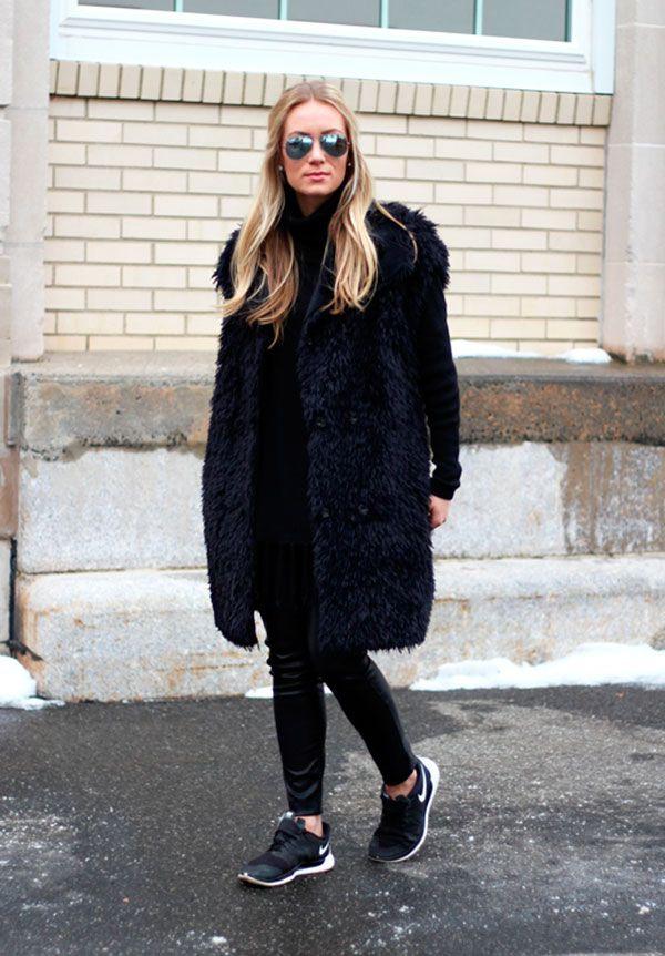 Street style look preto com colete longo de pêlo fake  e tênis.