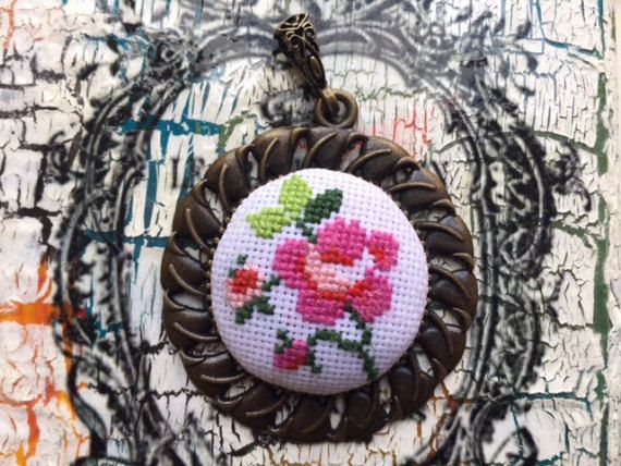A beautiful cross stitched flower pattern with different shades of pink and green. I can adjust the length of the chain if you like.