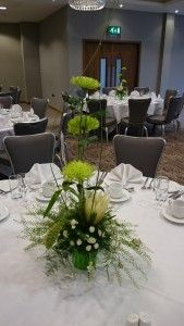 A round table setting with a central flower display of a cream protea, 3 green single chysants, stallion chrsants, setaria and ferns