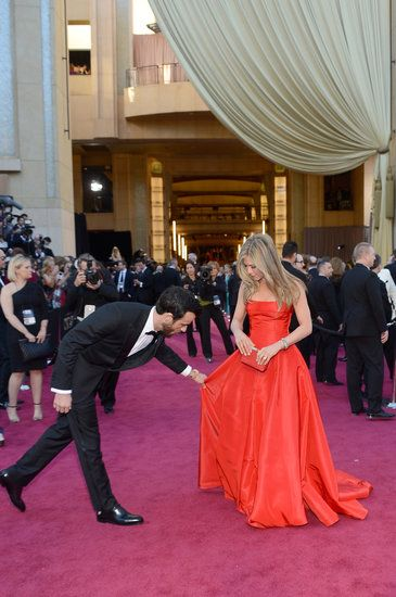The 20 Best Candid Oscars Red-Carpet Pictures: Justin Theroux was quite a gentleman, adjusting Jennifer Aniston's Valentino gown.