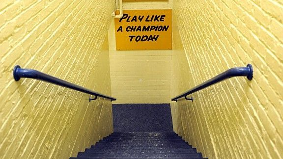 "The story behind Notre Dame's famous ""PLAY LIKE A CHAMPION TODAY"" sign and how it still helps the woman who painted it."
