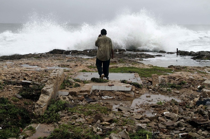 A man walks amid ruins of a home destroyed by Hurricane Sandy in Gibara, Cuba