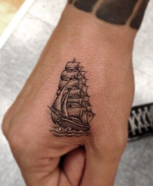 small ship tattoo on hand