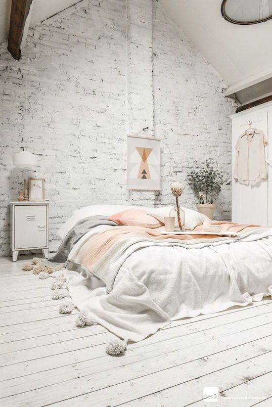 Winter decorating ideas – white bedroom with exposed brick wall and white wooden floor, pink accents