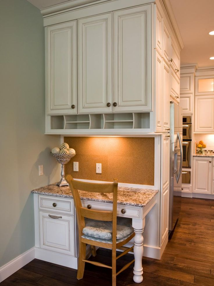 "This custom-designed kitchen desk area features plenty of storage, granite countertops and a corkboard ""backsplash."""