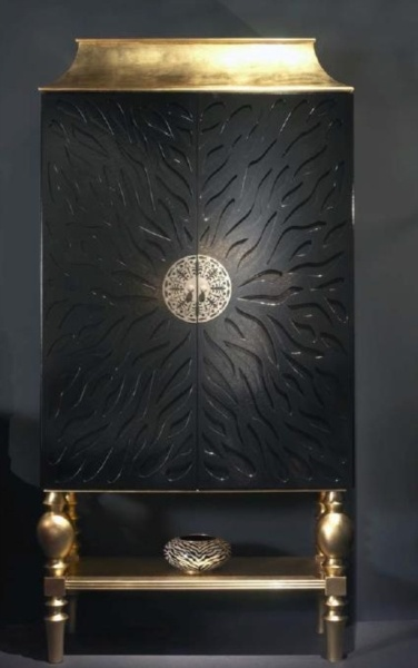 Intricately carved cabinet with a black finish and gold top and base