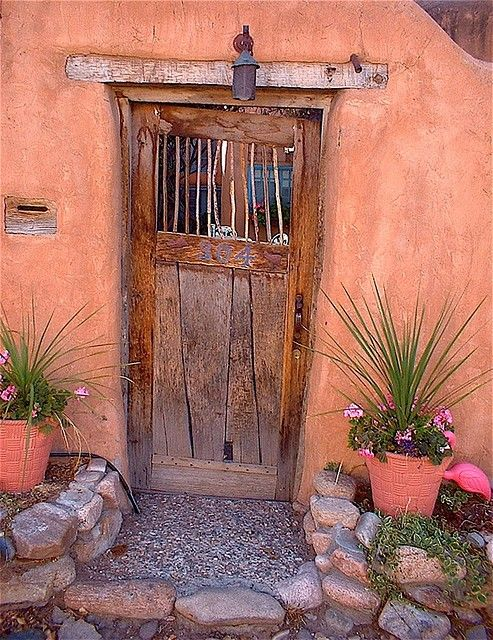 דלתות כניסה לא חייבות להיות מפוארות כדי ליצור אווירה  דלת כניסה זו בשילוב עם צבע הקיר המלבב והאדניות יוצר כניסה עם נשמה