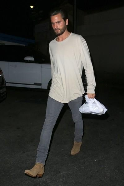 Scott Disick wearing Saint Laurent Hedi Jodhpur Boots, Saint Laurent Original Low Waisted Skinny Jean in Washed Grey Stretch Denim and John Elliott Ls Classic Curve Tee in Dove