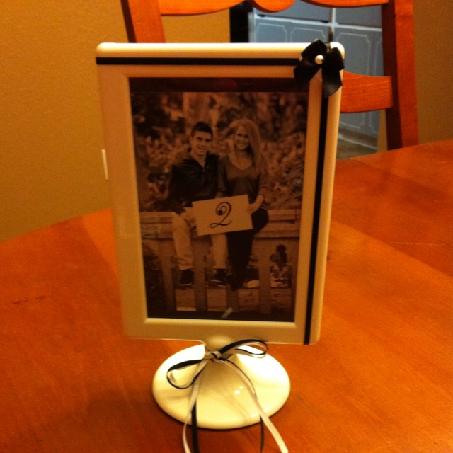 Wedding table number/centre piece idea. Picture frames from IKEA. Add a bow and a picture of the couple holding table numbers or a printed off sheet with the table number. $0.99