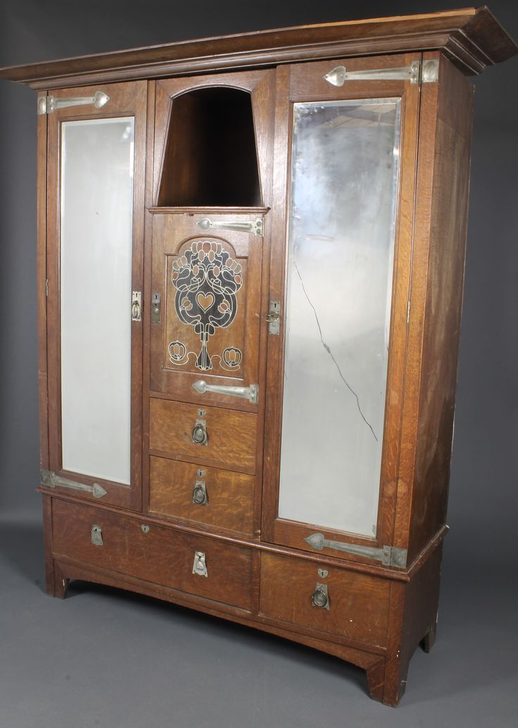 """Lot 1061, A Liberty's style Art Nouveau inlaid oak 2 piece bedroom suite comprising wardrobe with moulded cornice fitted 2 hanging cupboards enclosed by bevelled plate mirrored doors, the centre section with recess above cupboard and 3 long drawers, the base fitted 1 long and 1 short drawer 80""""h x 72""""w and a dressing table with rectangular plate mirror, fitted 2 short drawers above 1 long drawer, 64""""h x 45""""w x 21""""d, est  £100-200"""