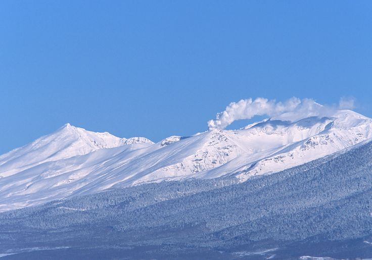 冬の十勝岳中富良野町 一面雪に覆われた十勝岳から、噴煙が立ちのぼっている。冬晴れの空の青と、雪山の純白とのコントラストは、雪国ならではの美しさ。夏に比べ、冬の方が山がくっきりとクリアに見える日が多い。