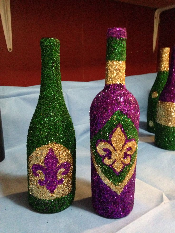 Wine bottles glittered for Mardi Gras decorations. Turned out gorgeous! Used Modge Podge, small paint brush, foam brush, glitter and design of choice.