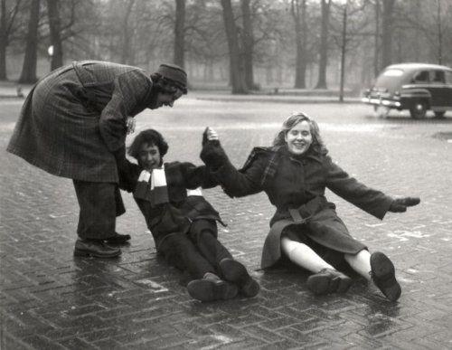 Twee kinderen moeten lachen nadat ze op straat zijn gevallen / onderuit gegaan ten gevolge van ijzel op straat. Een vrouw probeert ze weer overeind te helpen. Nederland, Haarlem, 11 december 1952.