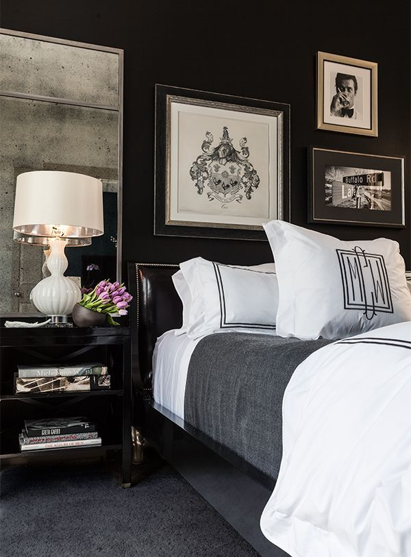 Love the dark walls the monogrammed pillow the black and white photos and framed family crest over the bed the mirror with an aged patina over the