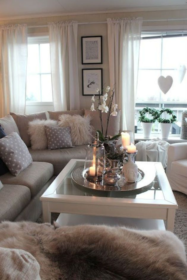 modern grey living room with cozy fur pillows and throws pretty candles and flowers on the coffee table tray