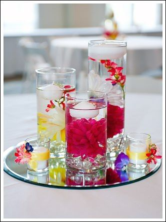 This idea is a wonderful way to add color and light to a table all at the same time. Simply place flower heads into the lower part of a cylinder vase, add water, and then place a floating candle on top. Taller centerpieces like these can be the main centerpiece or an accent to other floral wedding centerpieces.