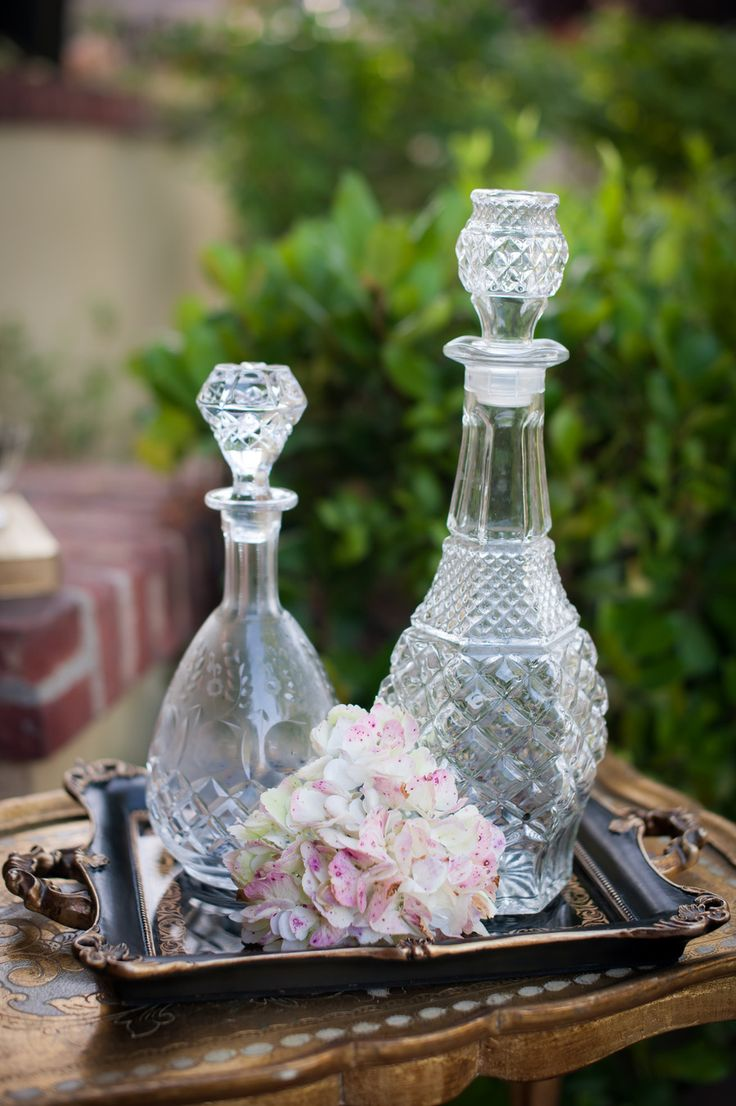 I have collected these decanters.  You could even tie a table number on a ribbon around the neck of each one.