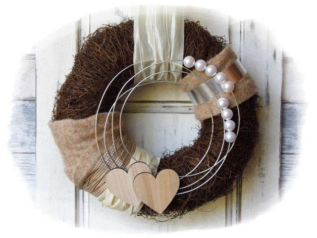**Wir bieten Ihnen einen tollen Türkranz zum Kauf an.**  _- Dekoriert ist der Kranz mit Schleifenbänder, Holzherzen, Perlen, Draht, Filz._  _Durchmesser ca. 35cm_ _Länge ca. 103cm_
