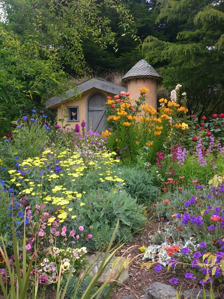 Sweet colorful old-fashioned English cottage garden!  Love the turret on the cottage and how the place is blended into its surroundings.