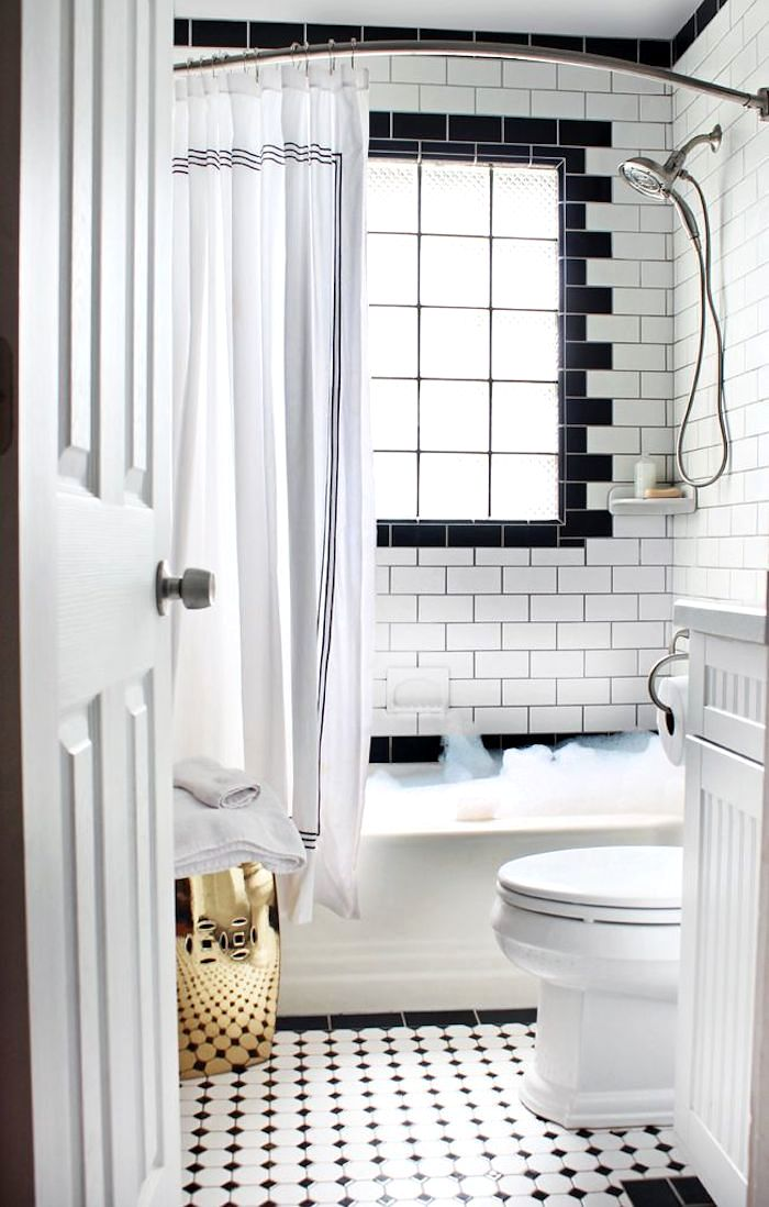 Pic On In addition to the traditional black and white tiled floor this bathroom from Hunted Interior boasts black subway tile borders around the tub window