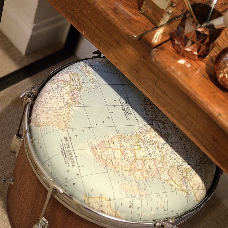 A vintage bass drum, which has been stripped back to the wooden body, with a seat upholstered in a world map printed Teflon coated fabric. This drum is thought to be approximately 50 years old and has the original metal hardware.These stools can be used as seating or footstools. The bass drum is the largest, lowest drum in the kit. Usually wider than they are deep, their dimensions lend themselves perfectly to seating and coffee tables.Our bass drum seats are approximately 60cm wide and 4...