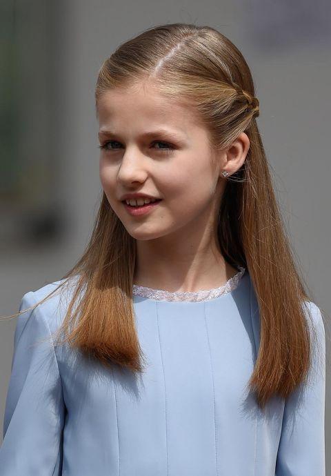 La Infanta Leonor llevaba un peinado muy parecido al de su hermana. Eligieron un semi-recogido que les retiraba el pelo de la cara, con la raya al lado y con trenzas laterales que se unían en la parte de atrás.