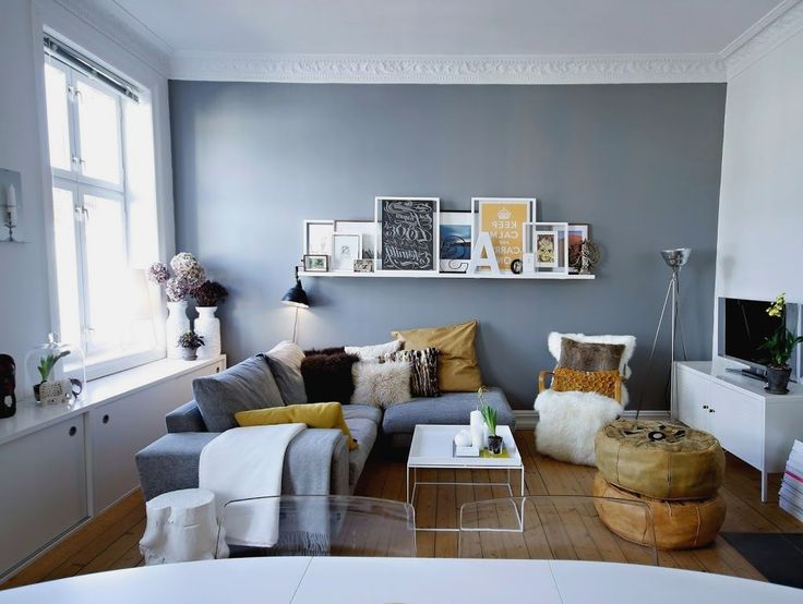 Piccolo salotto scandinavo con arredi colore bianco e grigio ed alcuni tocchi naturali: marrone chiaro e scuro