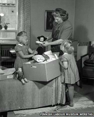Mother and daughters look at a pack from 1947- Why Finnish babies sleep in cardboard boxes