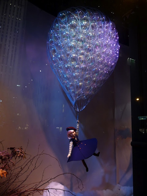At Saks Fifth Avenue: A blond girl catches a ride on a big balloon filled with water bubbles.