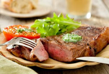 Grilled strip steak with compound butter - nicolebranan / Getty Images