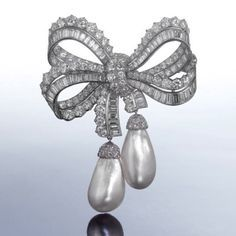 A rare diamond and pearl bow brooch, by Cartier, circa 1960 The looped ribbons set throughout with brilliant and baguette-cut diamonds.