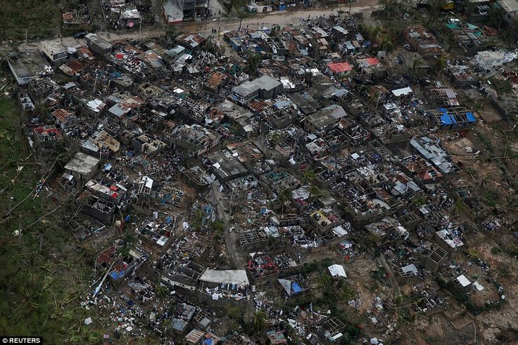 """#DailyMailUK ..... """"Amidst the rubble: People walk around near destroyed houses after Hurricane Matthew passes Jeremie, Haiti."""".... http://www.dailymail.co.uk/news/article-3825188/Devastation-Aerial-footage-shows-Haiti-villages-leveled-Hurricane-Matthew-death-toll-climbs-300.html"""