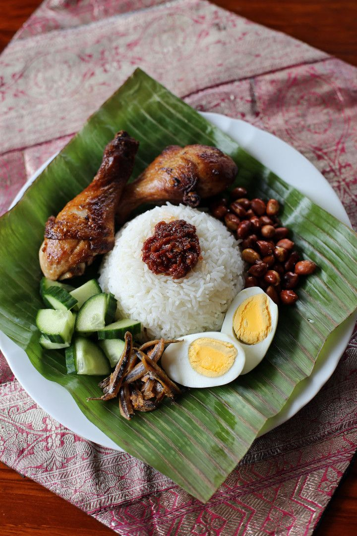 Nasi Lemak (Malaysia) - A rice dish served with cucumber, fried/hardboiled egg, fried anchovies, chicken, a fish cake, and chili sauce