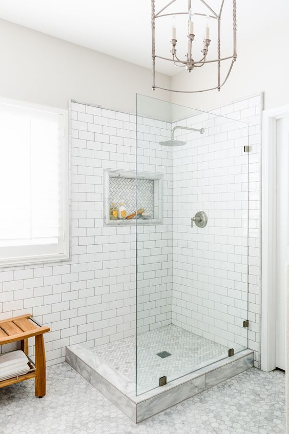 Master bath shower tile in a white subway pattern with gray grout, inset with marble herringbone tile, frameless shower, rainhead faucet.