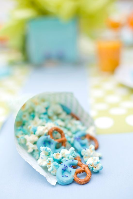 Monster Munch: Dip pretzels into melted blue candy melts. Sprinkle with purple nonpareils. Let pretzels cool on parchment or wax paper in the freezer. For candy coated popcorn, place freshly popped popcorn in a large mixing bowl. Using the leftover melted blue candy melts, drizzle over the popcorn and mix together with a rubber scraper until all of the popcorn is coated. Serve in a paper cone for aspecial little treat that all monsters like to eat!
