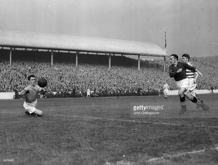 Celtic goalkeeper, Miller, dives for the ball during a Rangers attack, as Celtic play Glasgow Rangers in the Glasgow derby at Ibrox. Large crowds always gather for the 'Old Firm' matches between Rangers and Celtic. The importance of the event and the religious friction which has often accompanied these fixtures have led to disturbances both on and off the pitch. Rangers won this match 4-0. Original Publication: Picture Post - 4894 - Glasgow's Football War - pub. 1949