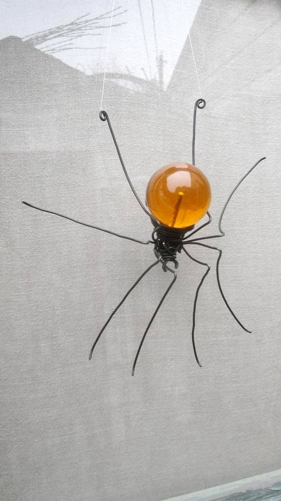 Orange Sun Catcher Window Spider Hanging Art Made to Order. She hangs motionless against the glass, her abdomen glows red in the sunlight streaming through the window. The vintage acrylic globe I used to create this beauty captures the world around her. If you stare into the depths of that orb you can see the world beyond the spider upside down. I will happily create a beautiful spider very similar to this one you! A length of thin wire is tied between her back feet. With a nail or a hook...