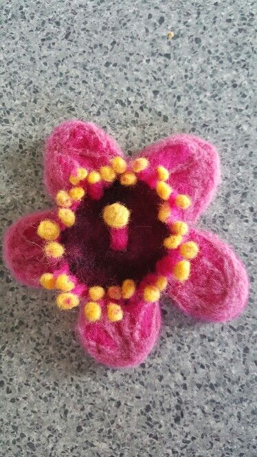 Wet and needle felted pink tea tree flower that will be an embellishment for a bag.