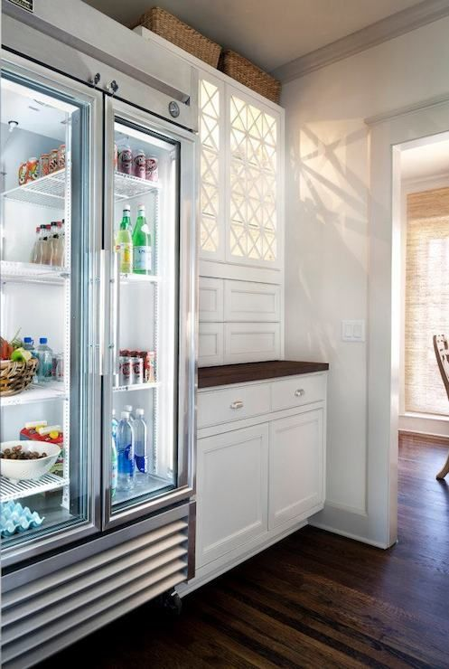 Kitchen features glass-door refrigerator next to built-in cabinets with decorative trim.