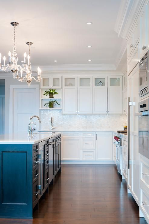 A pair of George II Chandeliers hang over a black kitchen island topped with Cambria Torquay Quartz fitted with a sink and gooseneck faucet. A black and white kitchen boasts white shaker cabinets paired with Cambria Torquay Quartz Countertops and a calacatta Moroccan tiled backsplash.